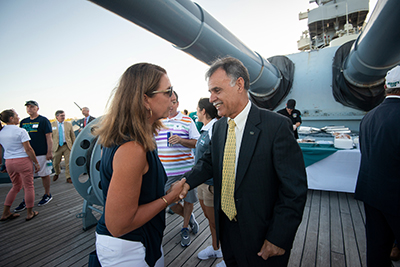 Chancellor Sartarelli (right) talks with women's basketball head coach Karen Barefoot (left) beneat the big guns of the Battleship North Carolina.