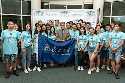Chancellor Sartarelli, center, with students from Fudan University in China and the University of the West Indies in Barbados, as well as ESL students from various countries on the steps of the Wise House