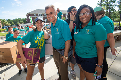 Chancellor Sartarelli with volunteers carrying boxes and belongings for first-year students during Move-In 2018.