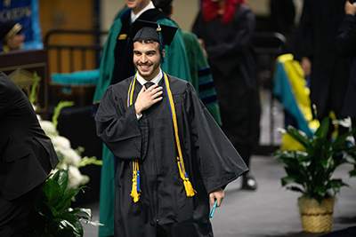 Male graduate with hand on heart smiles as he walks back to his seat