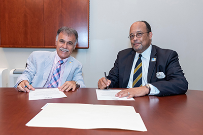 Chancellor and WCC President Thomas Walker Jr. signing agreement