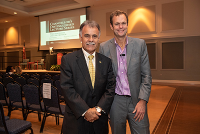 Chancellor Sartarelli (left) with Live Oak Bank President Huntley Garriott in front of a screen promoting the Chancellor's Distinguished Lecture Series.