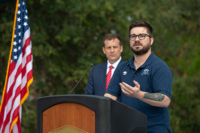 UNCW student Jay Richardson extends a tattooed arm as he speaks at the Veterans Day celebration. Bill Kawczynski, director of military affairs, is in the background.,
