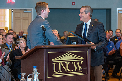 Student body President Cole Tillett '20 (left) presents a resolution to Trustee Carlton Fisher '83 in recognition of the contributions of his late father, Herbert Fisher '53, to UNCW.