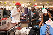 UNCW student and JC Penney associate look over choices in the men's business attire section.
