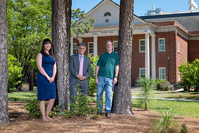 Kat Pohlman, Chancellor Sartarelli and Roger Shew in a stand of pine trees