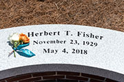 An engraved stone in memory of Herb Fisher.