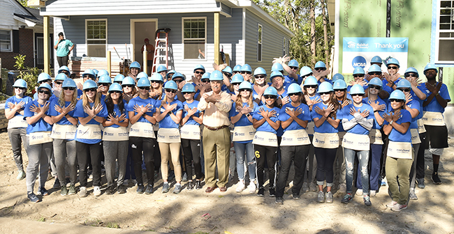 Chancellor (center, in hard hat) stands among a group of UNCW student-athletes in identical blue shirts and hard hats in front of a Habitat for Humanity House under construction.