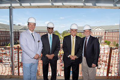 Left to right: Bill Kawczynski, Aswani Voleti, Chancellor Sartarelli and Charlie Hardy stand inside the structure of Veterans Hall overlooking McNeill Hall and the Teaching Lab.