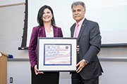 Ulku Clark (left) and Chancellor Sartarelli hold a framed certificate in a CIS classroom.