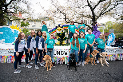 Sammy C. Hawk stands on the UNCW float, surrounded by UNCW students and Paws4People dogs on the ground below.