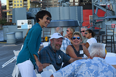 Women's Golf Coach Cindy Ho (left) leans over as she talks with a table full of fans on the Battleship North Carolina.