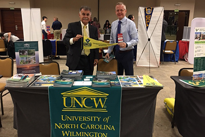 Chancellor Sartarelli (left), holding UNCW pennant, and Michael Wilhelm standing behind a table with UNCW banner.