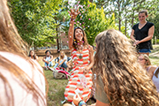 Michelle Britt (center) tosses confetti with students looking on in her outdoor classroom.