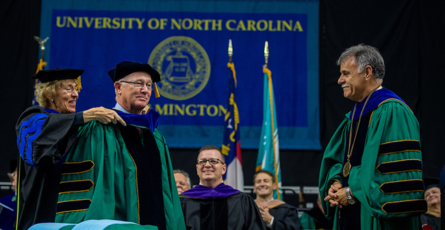 Provost Marilyn Sheerer (left) adjusts the doctoral hood for David Congdon '78 (center) who received an honorary Doctor of Business Degree in recognition of his contributions to his profession and to UNCW. Chancellor Sartarelli looks on at right.