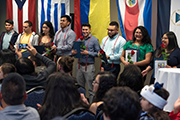A group of Centro Hispano students stands in front of international flags during a cording ceremony.