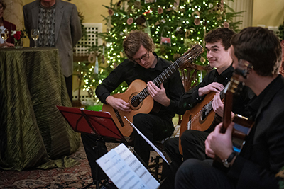 Three musicians in front of the holiday tree at Kenan House.