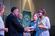Chancellor Sartarelli (second from left) shakes hands with Honors Medallion recipient (right).