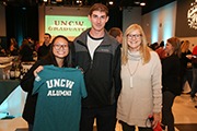 Female student (left) holding UNCW Alumni T-shirt, standing next to two other students at the Senior Toast.