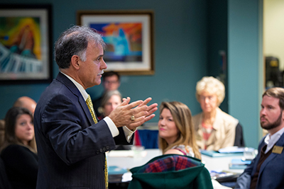 Chancellor Sartarelli addressing a group of education leaders.