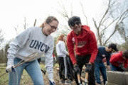 UNCW student and NC State student work together on a landscaping project.