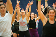 A group of women, arms raised, doing aerobic exercises.