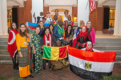 International faculty display colorful dress and national flags outside Kenan House.
