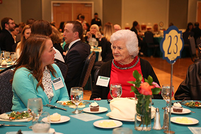 Donor and a student talk while seated at a table during the dinner.