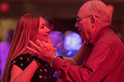 Older man dances with younger woman in red-tinted light.