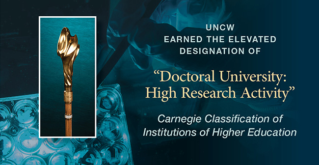 "Announcing new Carnegie Classification, ""Doctoral Universities: High Research Activity"" on teal backdrop with gloved hand and test tubes faintly in the background next to a cutout of the UNCW mace."