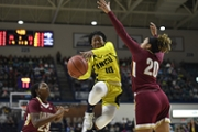 UNCW guard Ahyiona Vason drives past two Charleston players on the way to the basket.