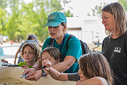 MarineQuest staff member (center) shows shellfish to the young children surrounding her.