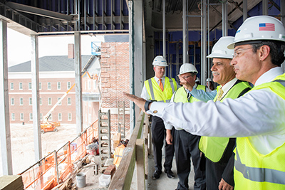 Wearing yellow vests and hard hats, Chancellor Sartarelli (second from front) and UNCW trustees look out on campus from the top of Veterans Hall, which is under construction..