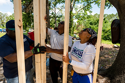 UNCW volunteers help frame a house or other building.