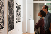 Two people admire large, black-and-white prints in the Cultural Arts Building gallery.