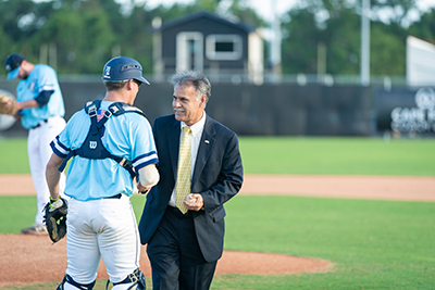 Chancellor, holding baseball, talks with UNCW catcher Zachary Bridges after tossing out the first pitch at the Sharks baseball game at Brooks Field..