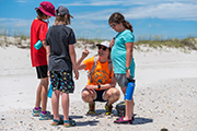 MarineQuest instructor Katelyn Sullivan, squatting, shows a shell or shark's tooth to a group of school-age students.