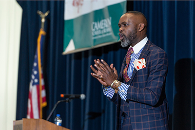 Derreck Kayongo gestures as he speaks during Business Week.