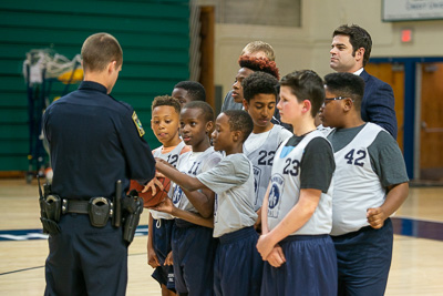Police officer/coach huddles with youth basketball players.