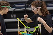 Students wearing goggles work on Rube Goldberg contraption.
