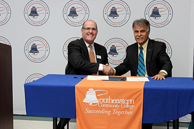 Anthony Clarke and Chancellor Sartarelli shake hands in front of Southeastern Community College backdrop..