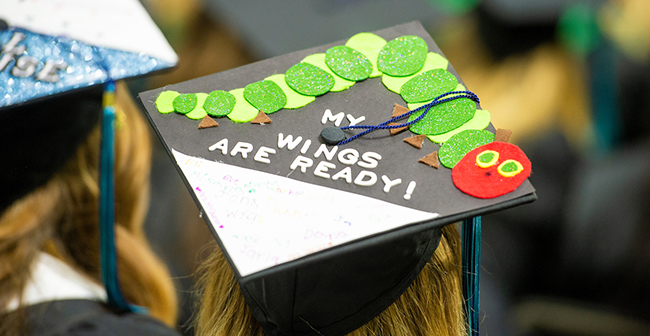 "Mortarboard cap with pasted-on image ofEric Carle's ""Very Hungry Caterpillar"" that reads, ""My Wings are Ready!"""
