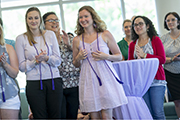 Student in lavender dress and lavendar cord with other students at Purple and Lavender Graduation.