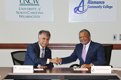 Chancellor Sartarelli (left) shakes hands with Alamance Community College President Algie Gatewood.
