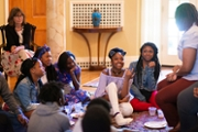 Kathy Sartarelli (left), children from Snipes Academy of Arts and Design (seated on the floor) and mentors from the Upperman Center.