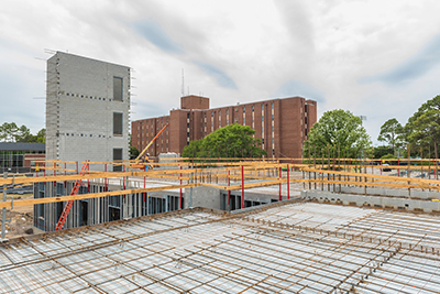 The concrete-and-rebar skeleton of the new student housing village is rising on the site of the old University Apartments.