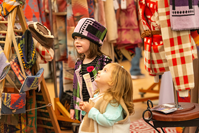 Two little girls look at colorful shawls, scarves and hats. One is wearing a matching knitted coat and hat.