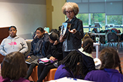 Carole Boston Weatherford holds up a book as she reads to several students.