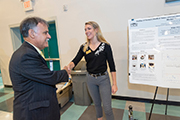 Chancellor Sartarelli (left) shakes hands with a student and admires her research poster.