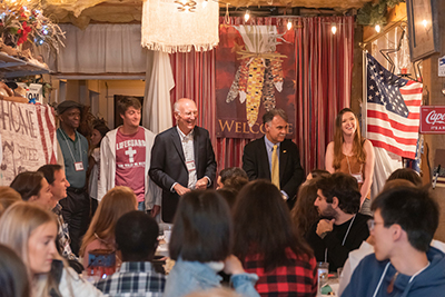 Tom Simpson (center) and Chancellor Sartarelli (on right next to Simpson), and tthree other people stand in Dr. Simpson's home, decorated for Thanksgiving. In the foreground are many international students.
